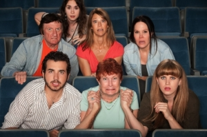 Group of scared people watching movie in a theater